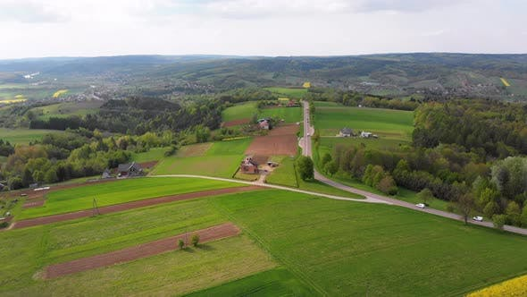 Thumbnail for Aerial Drone View of Green Fields, Hills and Trees in a Village with Small Houses. Poland.