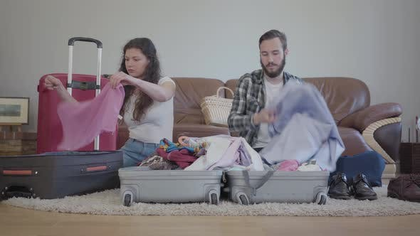 Thumbnail for Man and Woman Sitting on the Floor and Packing Them Cloth To the Big Suitcases