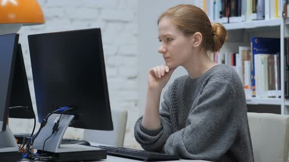 Thumbnail for Thinking Redhead Woman Working on Laptop, Sitting In Office