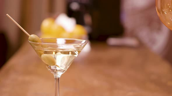 Thumbnail for Green Olives in a Glass of Martini on a Bar Counter