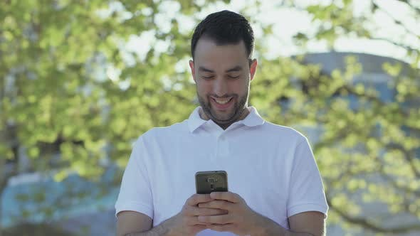 Thumbnail for Young Bearded Man Holding Smartphone and Laughing