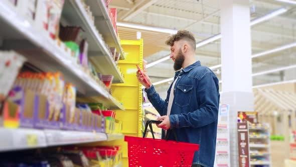 Sweet Department in Supermarket Man is Choosing Chocolate Reading Labels