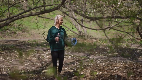 Wide Shot of Smiling Confident Senior Sportswoman Walking in Slow Motion in Summer Park with