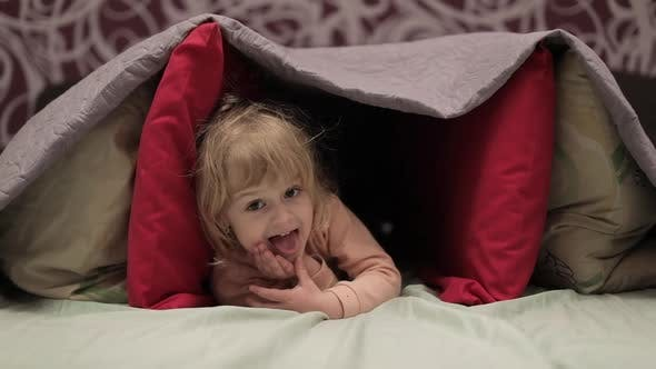 Thumbnail for Little Girl Hides Under Blanket and Pillows on the Bed. Concept of Hiding Place