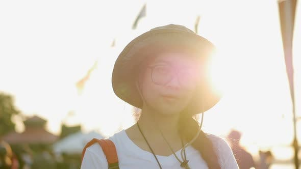 Young Asian woman smiling looking at camera over sunset background.