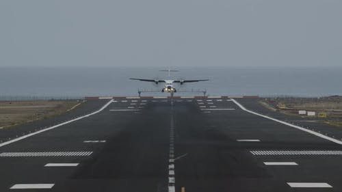 An Airport Runway with a Landing Plane