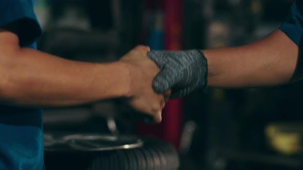 Professioneller Kfz-Mechaniker, der dem Autoservice-Kunden an der Reparaturstation die Hand schüttelt.