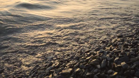 The Waves of the Sea Hit the Pebbles