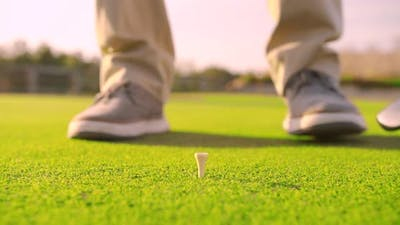 Golfer Placing Golf Ball on the Tee at Golf Course. Closeup