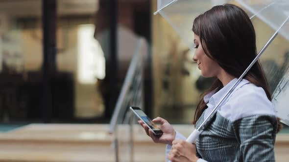 Thumbnail for Beautiful Young Business Woman Using Smartphone Walking on the Street in Rainy Weather