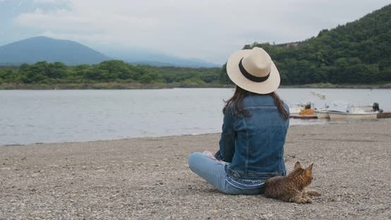 Woman sit at the lake side with a wild cat in shojiko of Japan