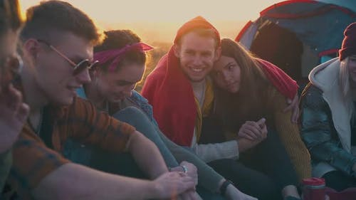 Happy People Spend Time Talking at Camp Bonfire at Sunset