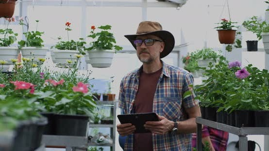 Thumbnail for Male Gardener Posing with Tablet in Greenhouse