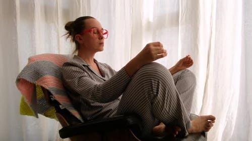 Woman in Pajama Meditating on Chair