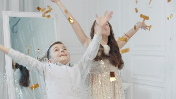 Thumbnail for Portrait of Happy Children Throwing Golden Confetti Into Camera.