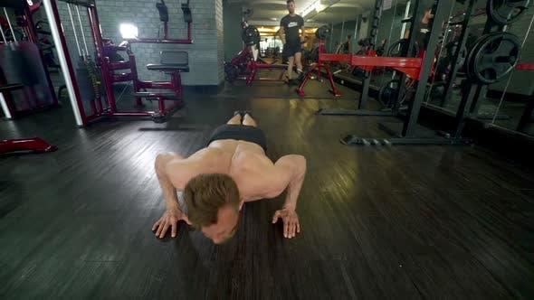 Mann Gesicht nach unten auf einem Hartholzboden tun Liegestütze während in einem Indoor-Fitness-Studio