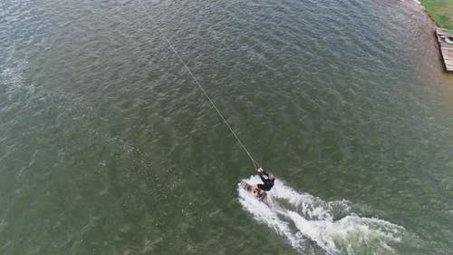 Wakeboarding, the Sportsman Surfs on the Water, Ride on a Wakeboarding Board and Performs Tricks