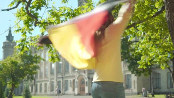 Thumbnail for Beautiful Redhead Woman in Eyeglasses Spreading Hands and Spinning with German Flag. Portrait of