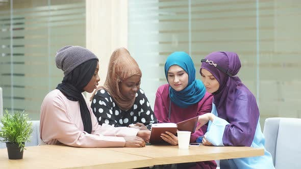 Cheerful Young Arabian Female Students Reading Book in Cafe.