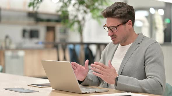 Sad Middle Aged Man Having Failure on Laptop in Office