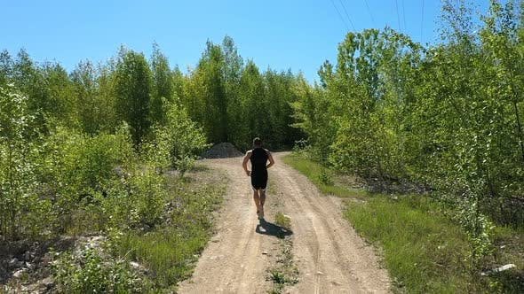Unrecognizable Sportsman Running Near Grove, Tracking Shot of Anonymous Male Athlete Running on Path