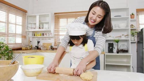 Young Asian family have fun cooking baking pastry or pie for breakfast meal in modern kitchen home.