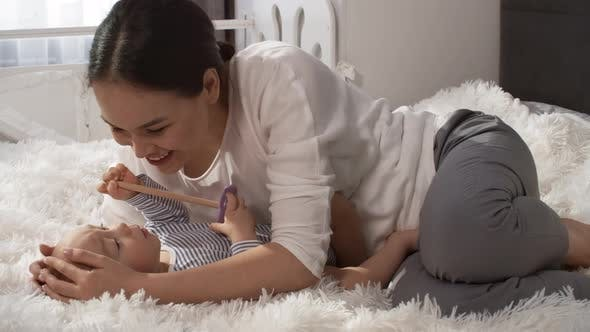 Affectionate Asian Mom Stroking and Kissing Baby