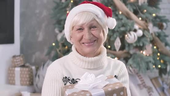 Thumbnail for Close-up Portrait of Positive Senior Caucasian Woman Holding Christmas Gift Box, Looking at Camera