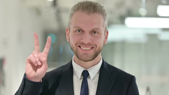 Thumbnail for Portrait of Successful Businessman Showing Victory Sign with Hand