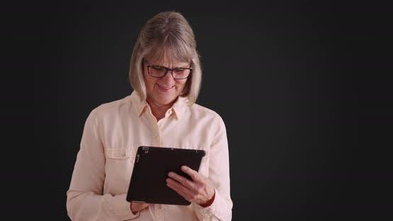 Joyful laughing senior woman enjoying using pad device on grey backdrop