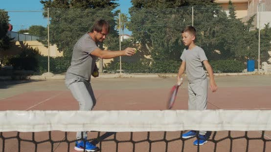 Cover Image for Child Traning in Tennis. Father and Son Practice Blows in Tennis on Coart. Active Leisure Together.