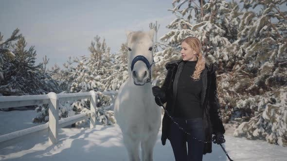 Thumbnail for Blonde Strokes and Feeds a White Horse on a Snowy Country Ranch