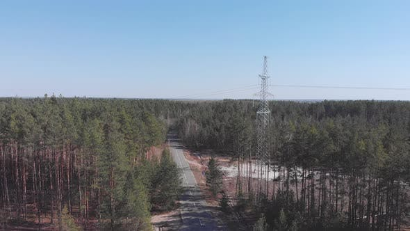 High-voltage electricity power lines in green forest. Transmission tower