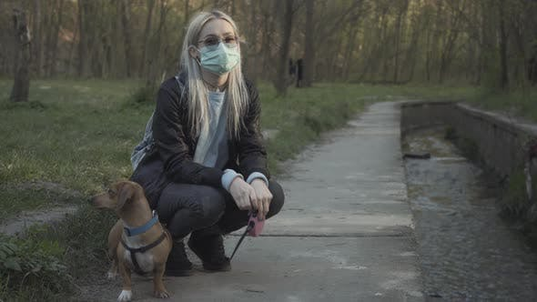 Thumbnail for Young Blond Girl in Face Mask and Sunglasses Sitting on Hunkers in Park and Talking To Small Dog