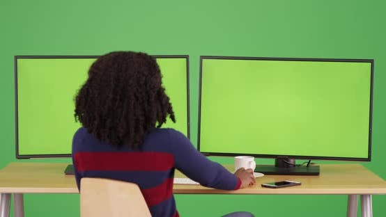Thumbnail for Rear view of black female on green screen working on computer with greenscreen