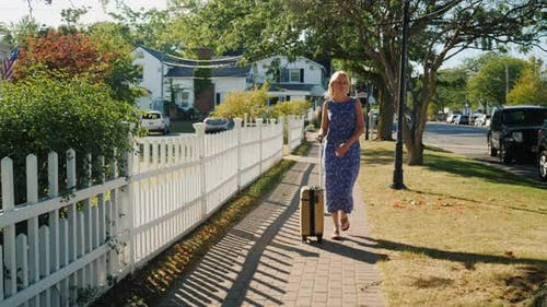 A Woman with a Travel Bag on Wheels Is Walking Along the Sidewalk. A Typical American Town