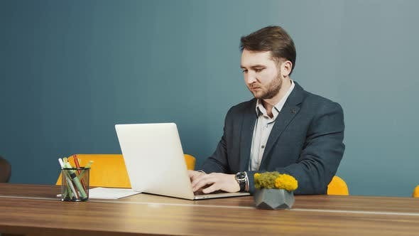 Young Bearded Man Programmer Caucasian Appearance Sitting and Working on a Laptop