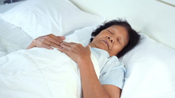 old woman sleeping on a bed in bedroom
