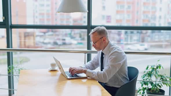 Thumbnail for Side view of a senior man typing on a laptop