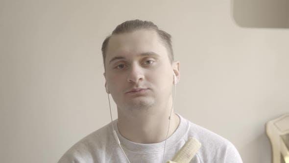 Thumbnail for Nahaufnahme von Brown-eyed Brünette Mann Essen Banane. Porträt von jungen kaukasischen Kerl in Ohrhörern