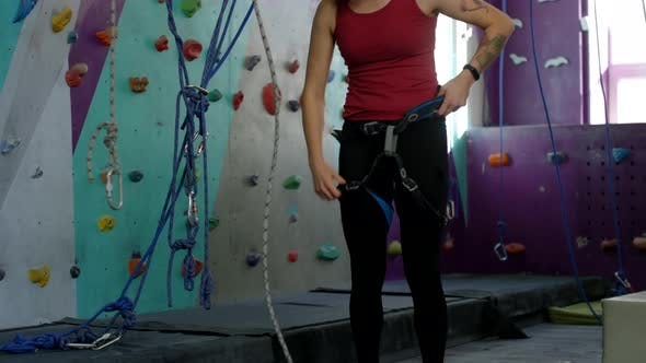 Thumbnail for Young Female Climber Putting on Safety Harness at Indoor Gym