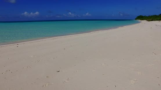 Wide angle birds eye copy space shot of a sunshine white sandy paradise beach and blue water backgro