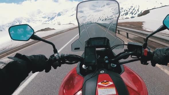 Motorcyclist Rides on Beautiful Landscape Snowy Mountain Road Near Switzerland Alps