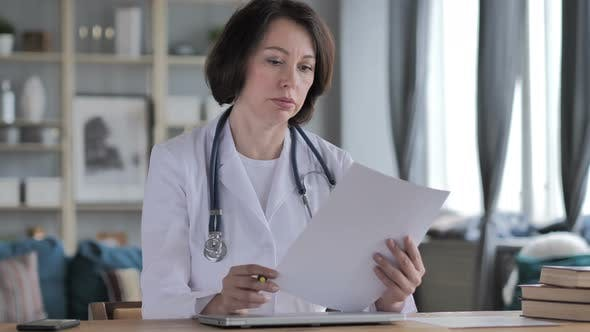 Thumbnail for Old Lady Doctor Reading Medical Report, Paperwork