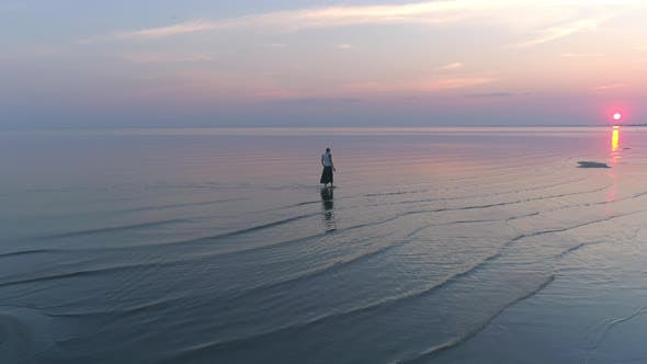 Thumbnail for Woman Walking in Sea Water at Sunset