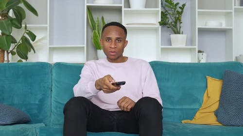 Happy Young African Ethnicity Man Relaxing on Cozy Sofa at Home, Holding Remote Controller, Watching