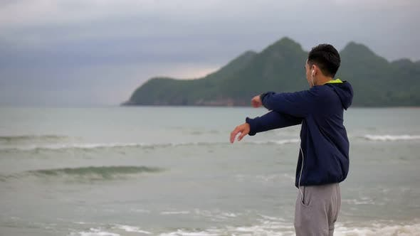 Handsome man running on the beach, Sportsman stretching before running along the beach.