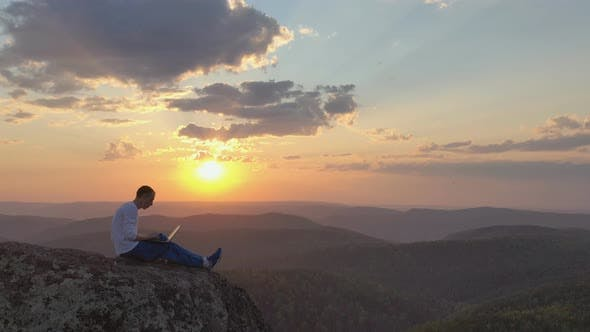 Thumbnail for Epic Drone Shot of a Silhouette of a Young Freelancer with a Laptop on the Edge of a Rock Ledge in