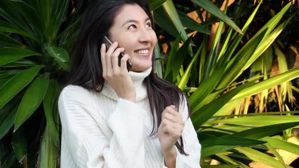 Thumbnail for Slow Motion Young Asian Woman Use the Phone with Earphones While Walking