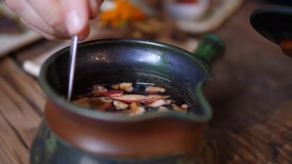 Thumbnail for Nahaufnahme von heißem Tee in einer traditionellen Teekanne. Blumen und Stücke von Trockenfrüchten auf Teelöffel.
